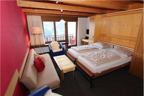 Wohnbereich mit Klappbett und Balkon