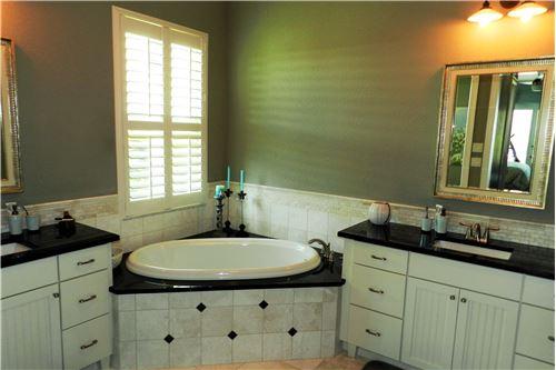 Badezimmer mit Badewanne, Dusche, WC und zwei Lavabos