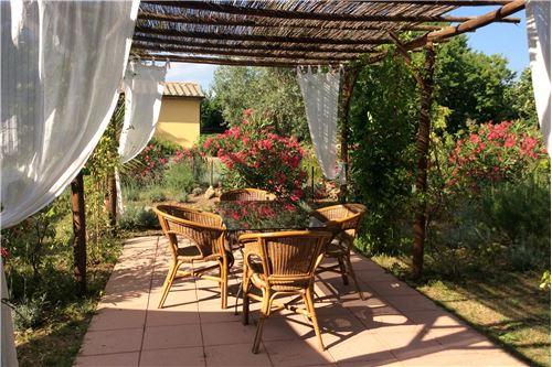 Grossflächige Terrassen mit Plattenböden, eigener Garten mit Wein-Pergola.